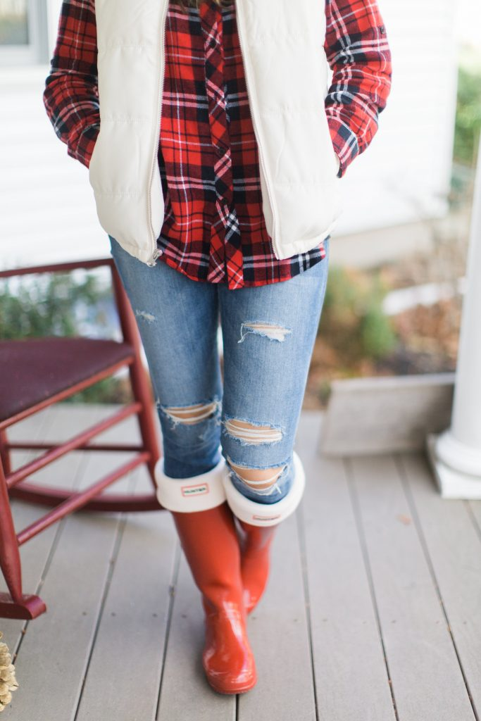 A casual holiday outfit with a plaid shirt, white puffer vest, and red Hunter boots is perfectly comfortable and festive.