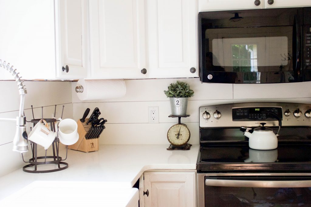 Farmhouse kitchen with shiplap walls, quartz countertops, and vintage accents