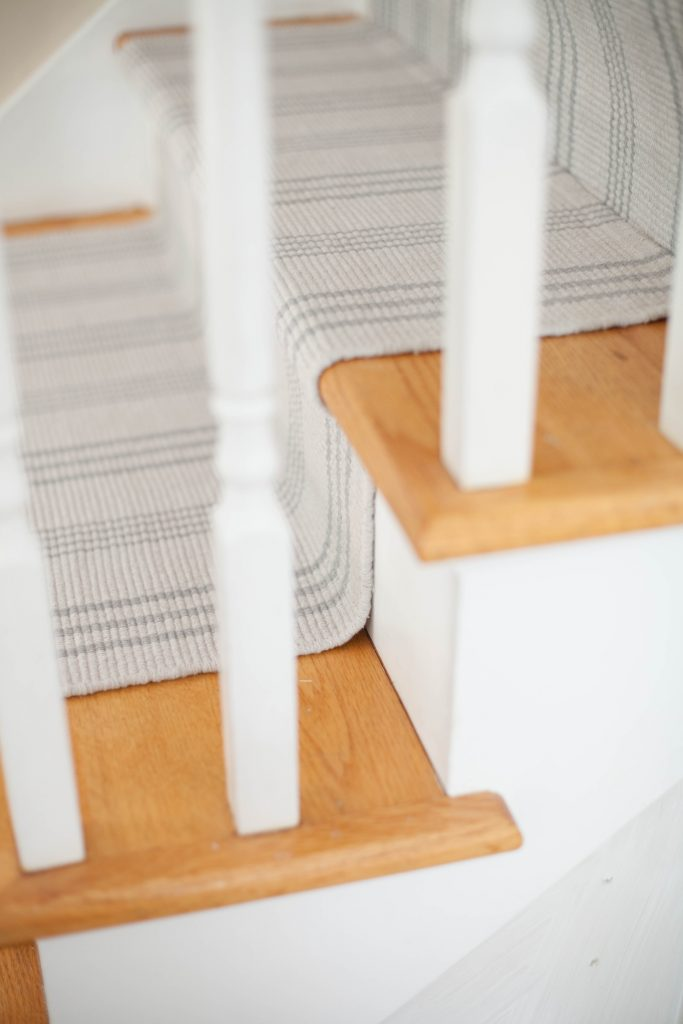 A simple guide to making a DIY stair runner using area rugs and carpet tape for a low cost solution for loud stairs!