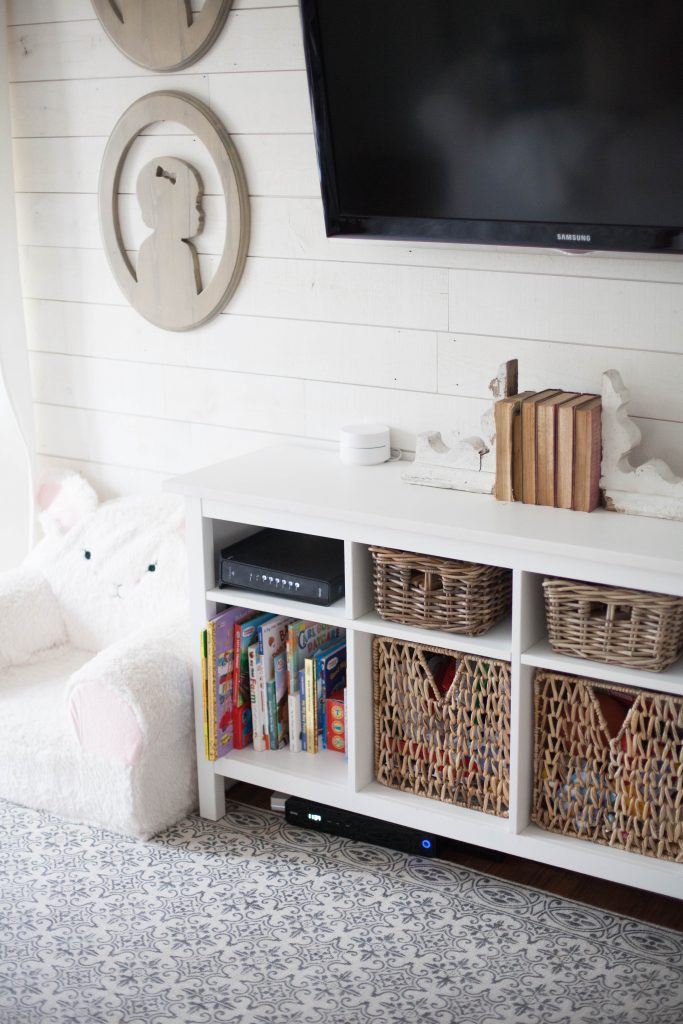 A cottage style playroom that functions as a family room as well, while keeping it kid-friendly with a variety of storage options for easy pick up.